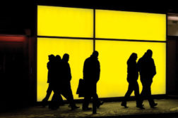 People walking in front of a yellow window