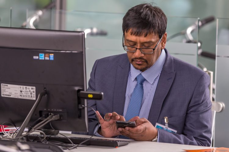 Man sits at computer facing camera