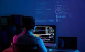 Man coding at desktop computer
