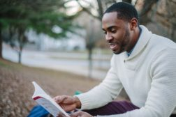 Young professional reads outdoors