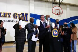 California governor Gavin Newsom stands with officials after signing police reform bills