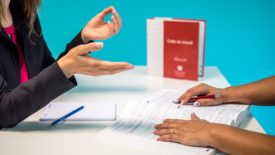 Hands over desk, employees talk
