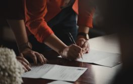 Two people sign a contract