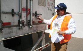 A Ryder employee checks the securement of a load in transit