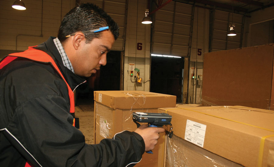 A Ryder warehouse employee receives and scans a shipment